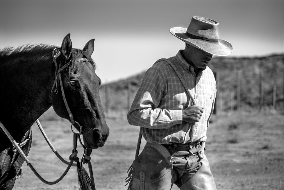 cowboy wearing chaps leading his horse with lead line draped over shoulder