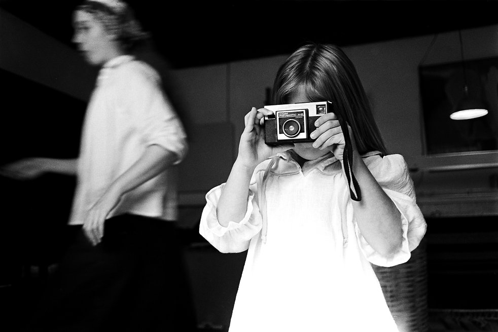 young girl taking picture with a kodak instamatic camera