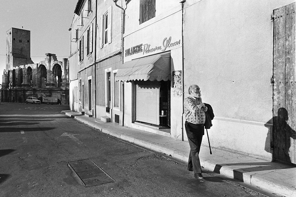 man walking down street with roman coliseum in the background