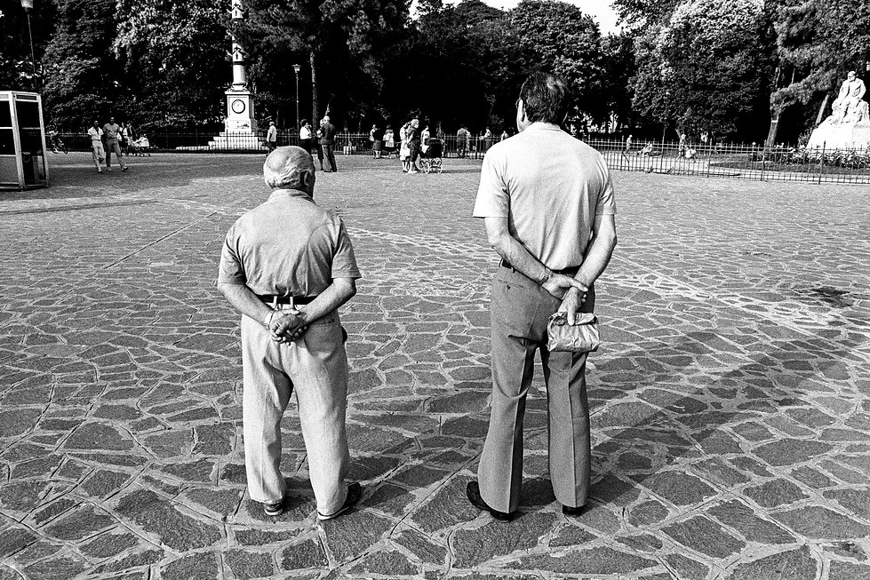 two men standing side by side while people watching in Venice