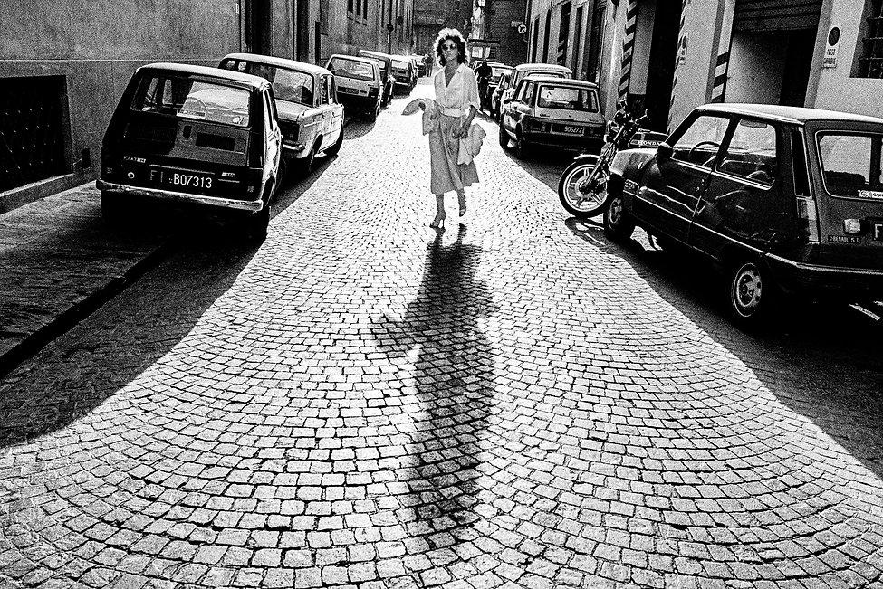 Woman walking on cobble street near the Uffizi Museum, Florence