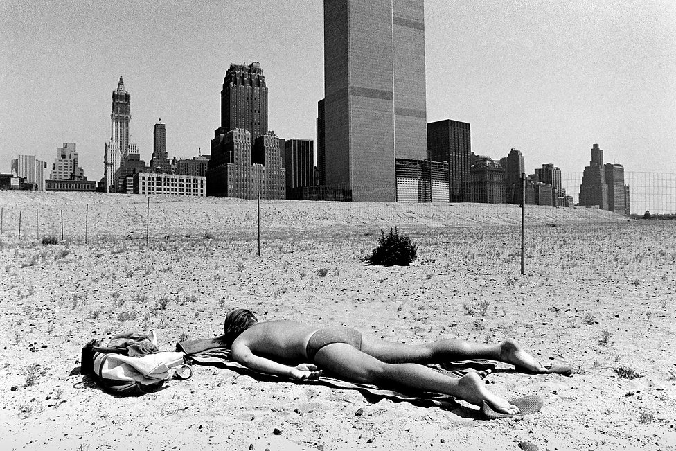World Trade Center with man sunbathing on the south beach Manhattan