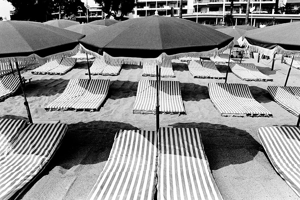 Rowes of beach umbrellas and striped chaise, Cannes xx