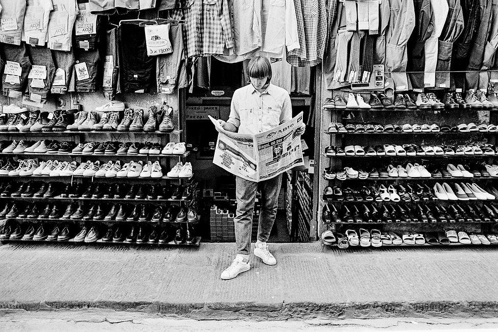 Sales staff member reading newspaper on sidewalk in front of shoe and clothing store, Florence