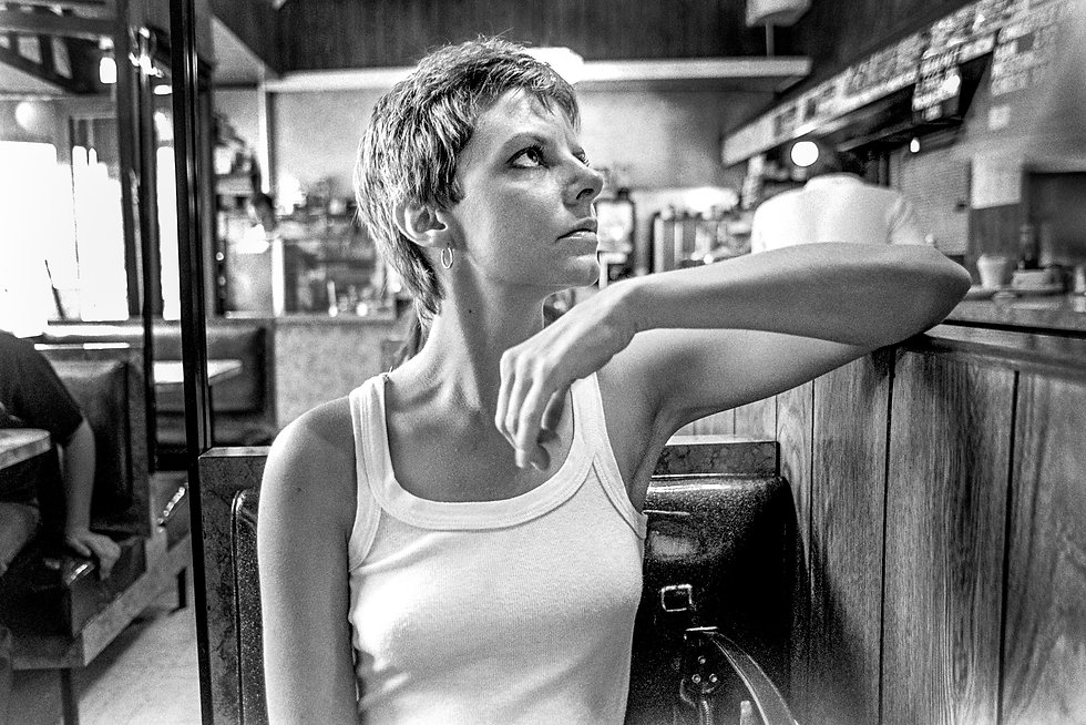Woman with tank top and short hair in a New York City diner