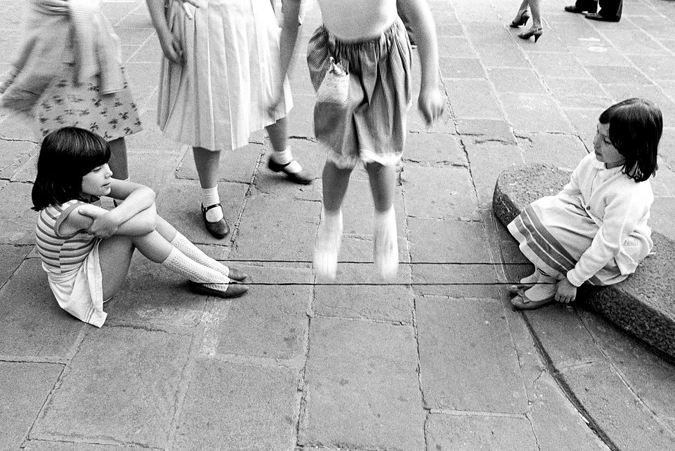 young girls playing jumprope on plaza in the gothic quarter in Barcelona