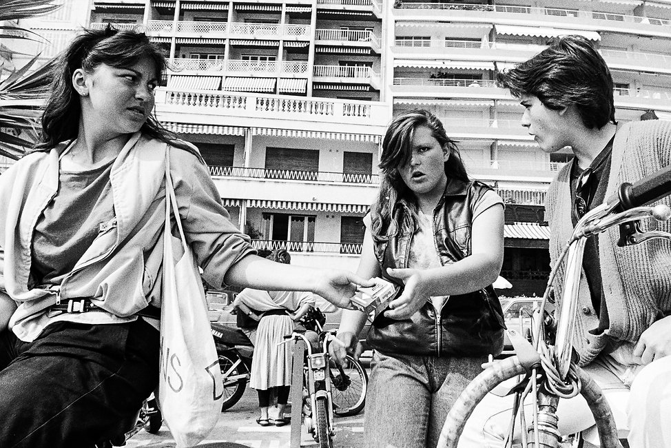 Three teenagers in Cannes passing box of  Marlboro cigarettes