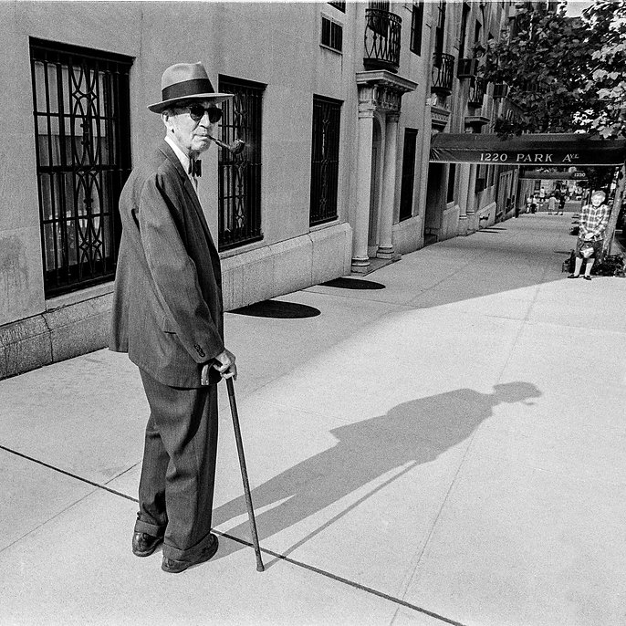old man with a cane wearing a suit, sunglasses, a fedora, smoking a pipe, on Park Avenue New York City