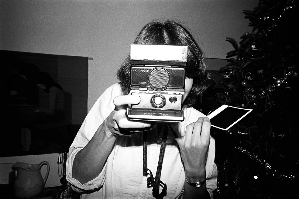 woman taking photograph  with a polaroid camera