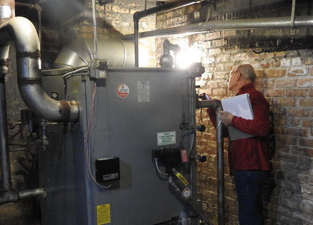 Volunteer Jim Cavallo inspects a furnace on an energy audit.