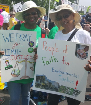 Velma Pate and a friend show off their signs at the People's Climate March.