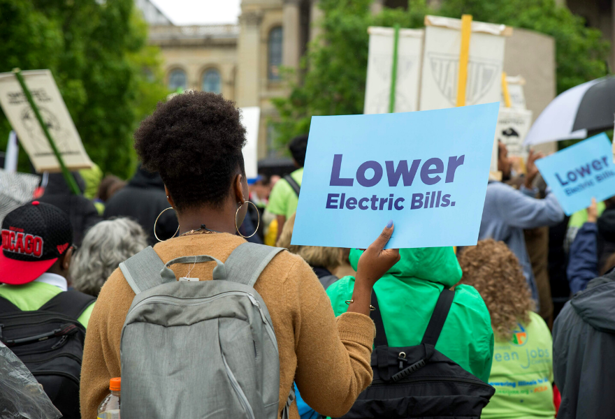 "Spring 2019 Advocacy Day Rally at the IL State Capitol features a person holding a sign that reads, ""Lower Electric Bills""."