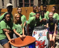 Eco-Ambassadors pose with rain barrels they painted.