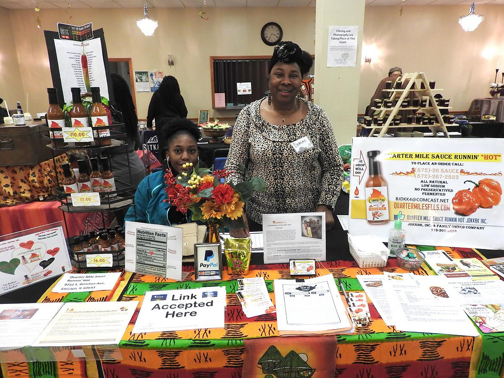 Dorcas Bishop, Owner of Quarter Mile Runnin' Hot Sauce, and her granddaughter at the Winter Farmers Market