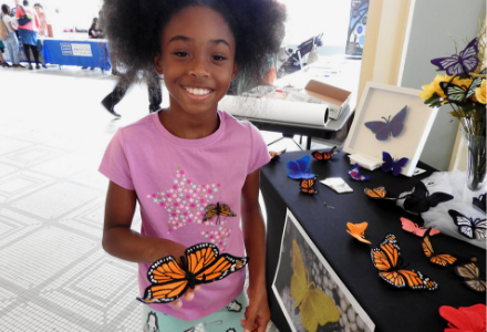 A young participant enjoys the butterfly artwork.