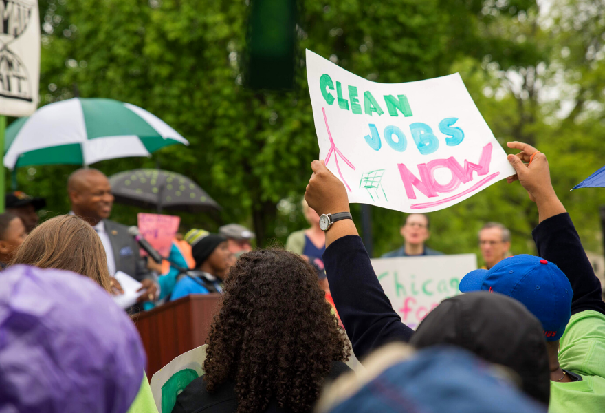 "Spring 2019 Advocacy Day Rally at the IL State Capitol features a person holding a sign that reads, ""Clean Jobs Now""."