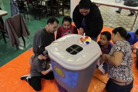 Adults & kids paint a rain barrel.