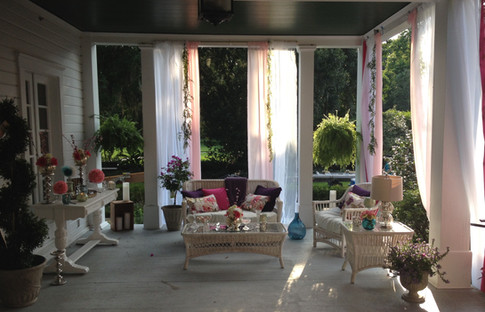 This was the front porch of a plantation home we dressed and decorated to simulate a wedding. We hung drapes, covered the cushions in our own fabric and brought in our own greens and floral touches.