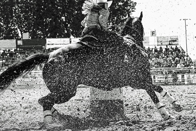 A barrel racer at a rodeo makes an explo