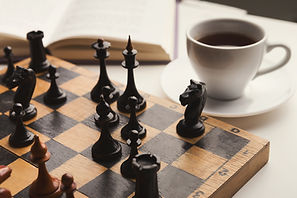 wooden-desk-with-chess-play-book-and-cof