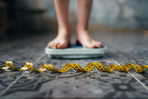female-feet-on-the-scales-measuring-tape