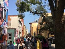 Street crowded with people enjoying art