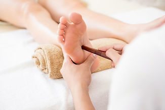 Professional therapist giving traditional thai foot massage with stick to a woman in spa.j