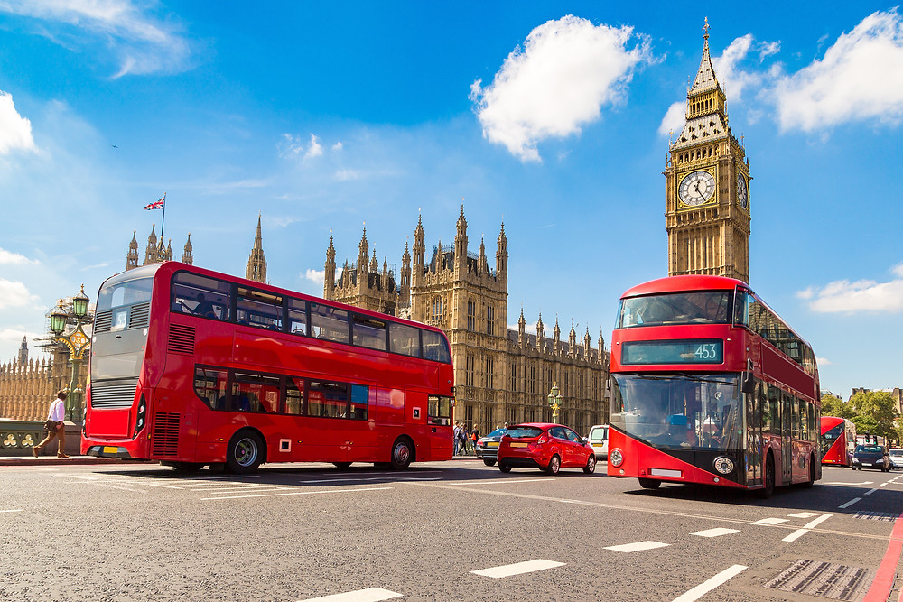 Westminster Palace towers over the streets of London with two red buses passing by.