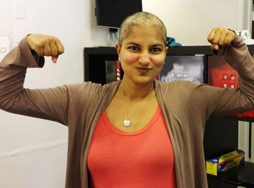 Parul showing strength with her shaved head during cancer treatment.