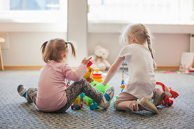 two-little-girls-sitting-floor-playing.j