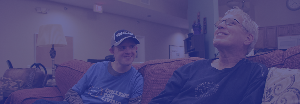 Two men with developmental disabilities hanging out on a couch.
