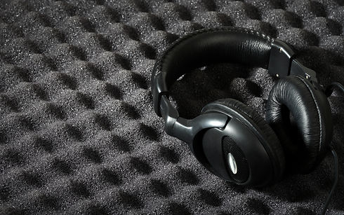 Professional headphones lying on acoustic foam with an egg-crate pattern.