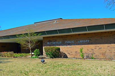Photo of the front of Blytheville Public Library, a red brick building with sloping roof. The bottom of the skylight is outlined against a clear blue sky; a bit of green grass and landscaping shows in the foreground