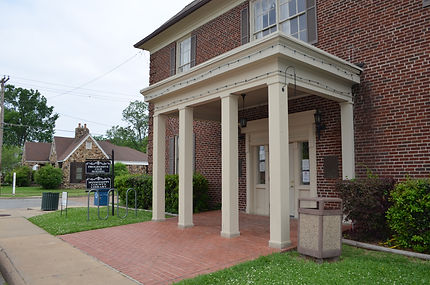 Front door of the Osceola Public LIbrary, a 2-story red brick building that is nearly 100 years old. The double front doors are painted white and the brick walkway is overhung with a white portico, supported by four square columns. The library building is on a street corner; a neighboring stone building can be seen in the picture's background