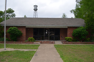 Picture of the Keiser Public Library. A sidewalk between two patches of grass leads to the front door (accesible by stairs and a ramp). Door is surrounded by full-length windows. Building is red brick with a brown roof. Front yard has a flag pole; water tower is visible in the background, over the library's roof