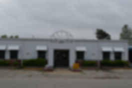 Front of the Leachville Public Library, a white-framed building that is shared with the Leachville branch of Arkansas Northeastern College. Door is framed with a metal arch; windows are overhung with white parapets. The picture was taken on a cloudy day; the sky is gray and almost uniform in color with the building