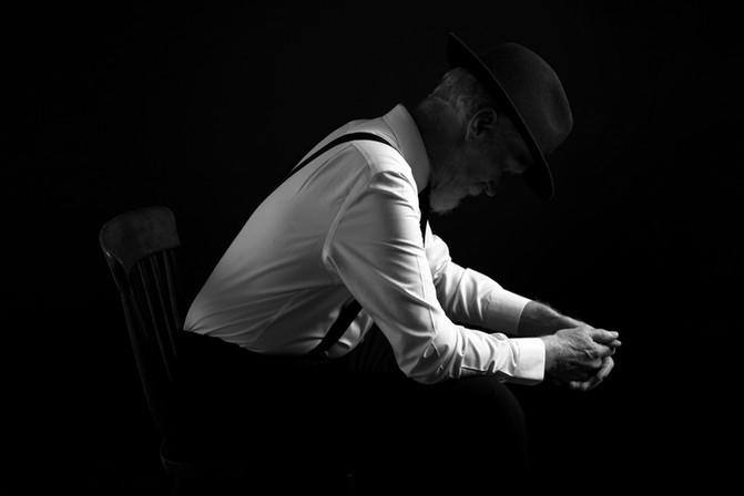 Black-and-white-portrait-photo-of-a-male-model-on-a-black-backgorund