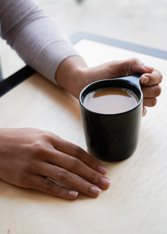 manicured hands holding coffee cup