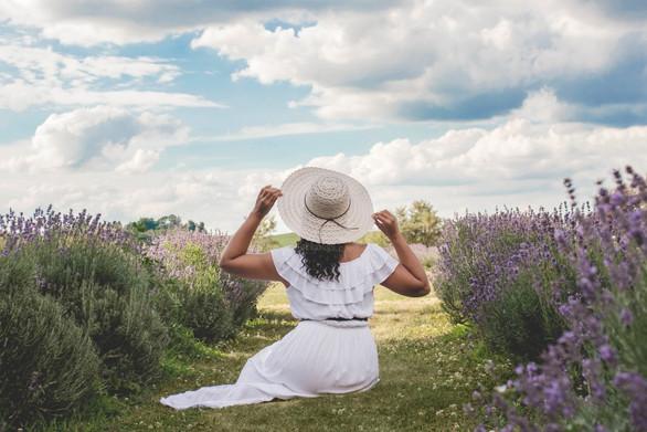 model holding white hat in lavendar field