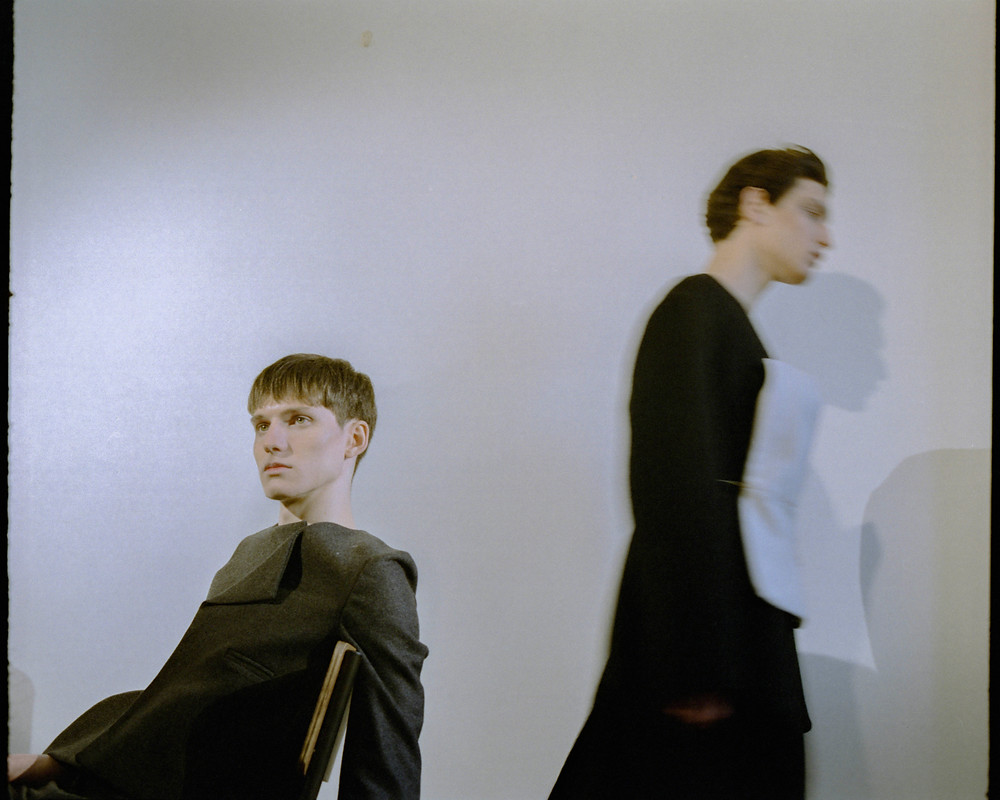 Alex wears Victoria Valette suit Aleksander wears top and draped black coat by Lazkano.