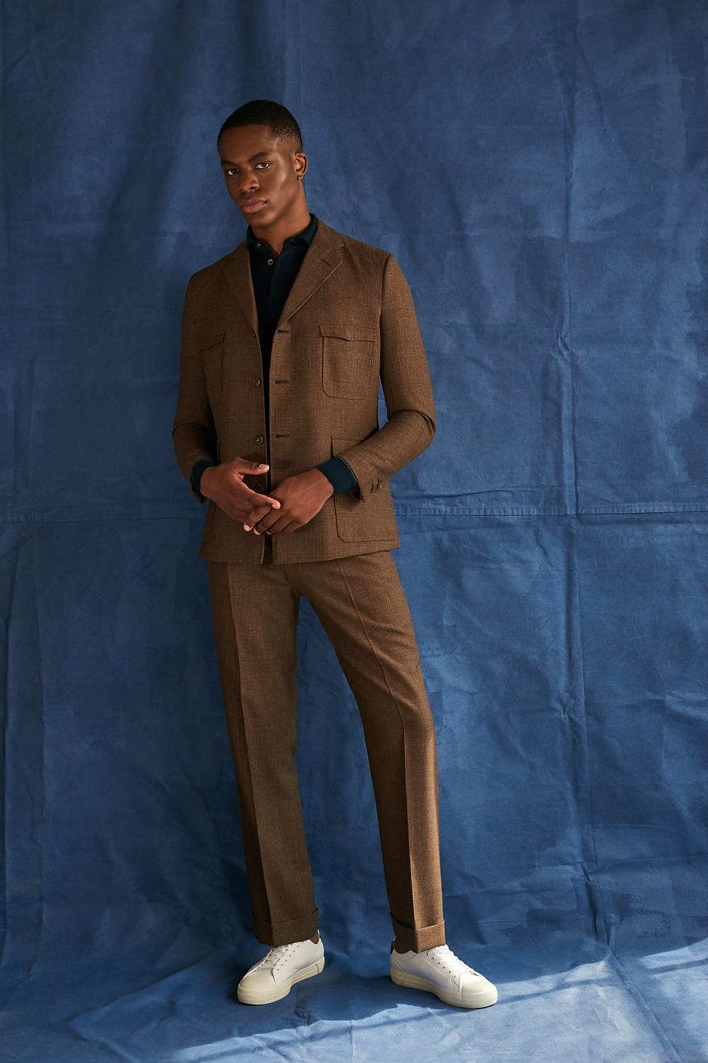 Richard Anderson Brown Checked Safari Trouser Suit; John Smedley Merino Wool Polo Shirt; Lacoste Gripshot Trainers