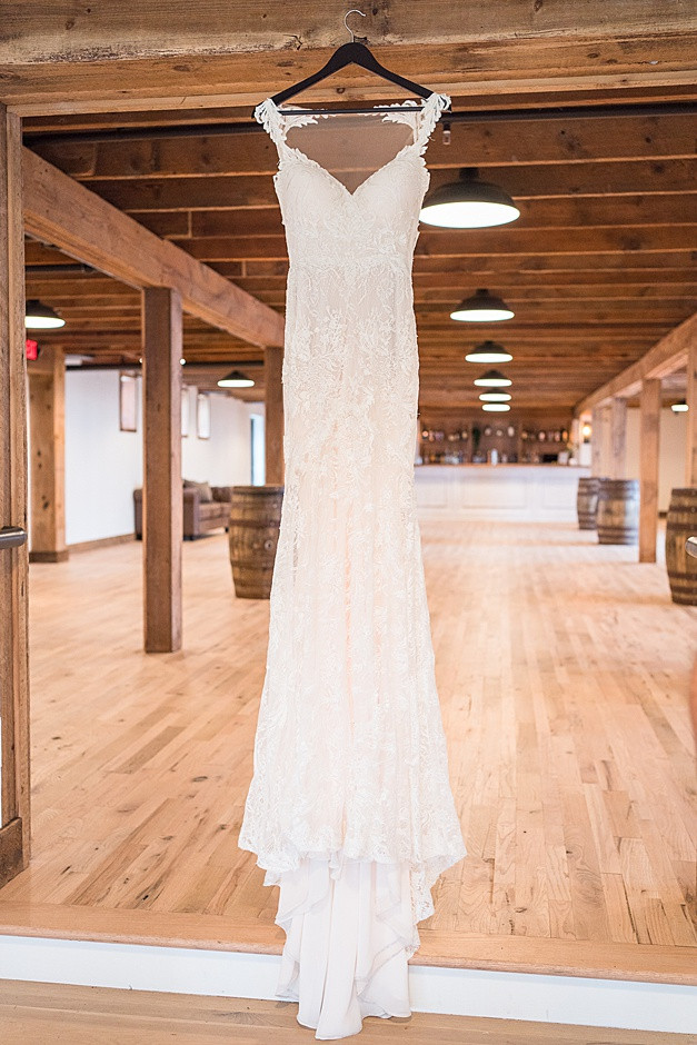 A wedding dress, a designer wedding dress, a wedding dress with lace, the wedding gown has a sweetheart neck, train of a wedding dress,in a bright light wedding venue in Wisconsin