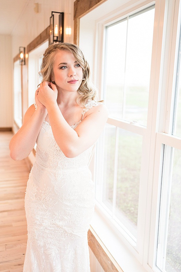 Bride putting on an earring wearing a wedding dress, a designer wedding dress, a wedding dress with lace, the wedding gown has a sweetheart neck, train of a wedding dress,in a bright light wedding venue in Wisconsin