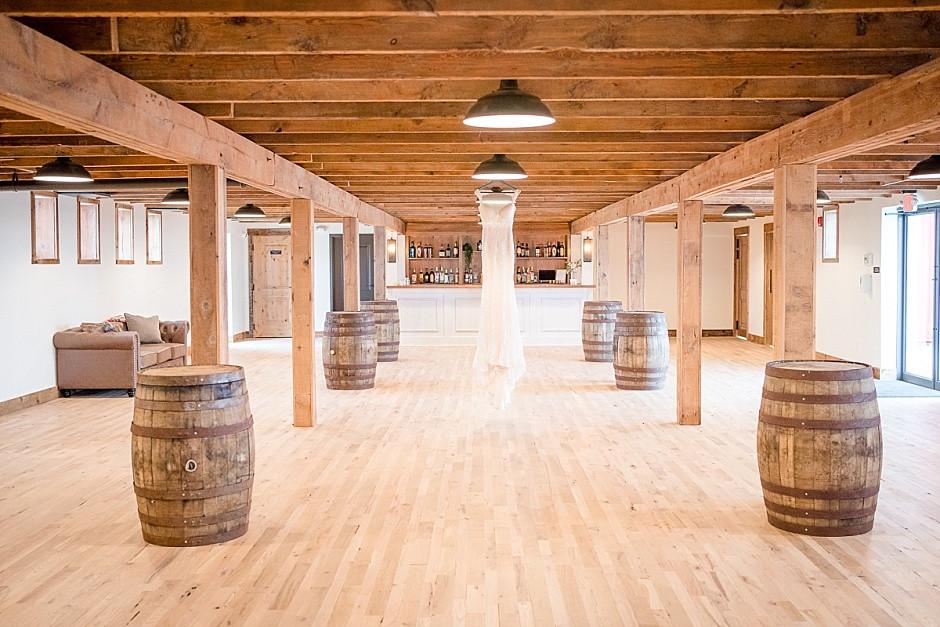 barn wedding venue, open indoor wedding reception area, indoor wedding venue wisconsin, indoor cocktail area wisconsin, wood elements, with wedding dress hanging
