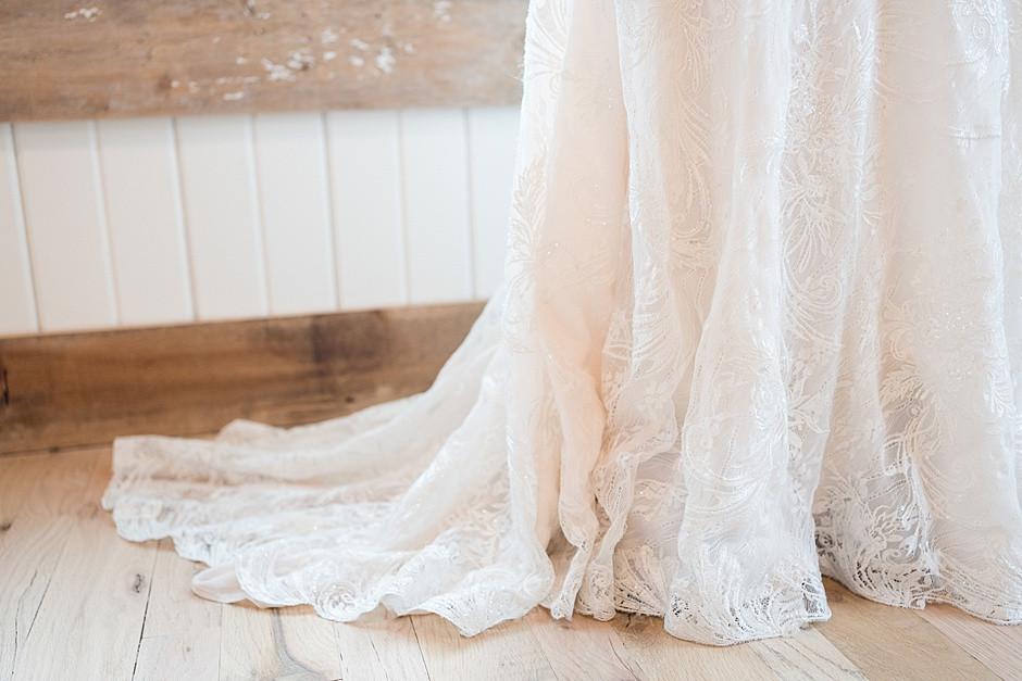 A wedding dress, a designer wedding dress, a wedding dress with lace, train of a wedding dress,in a bright light wedding venue in Wisconsin