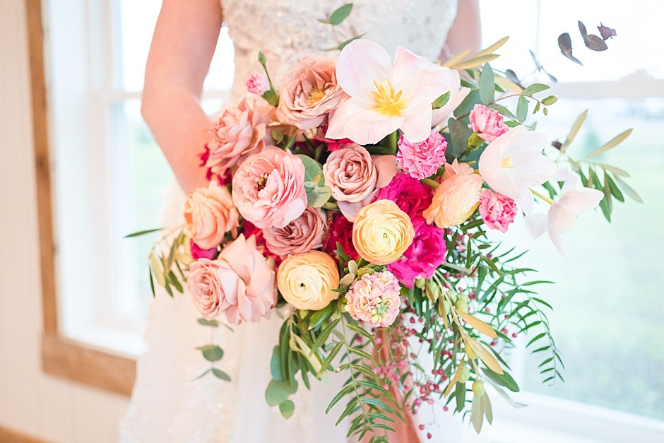 Bright floral, bridal bouquet of ranunculus, pink roses, cappuccino roses, eucalyptus, white tulips, whimsical wedding flowers bride holding bouquet