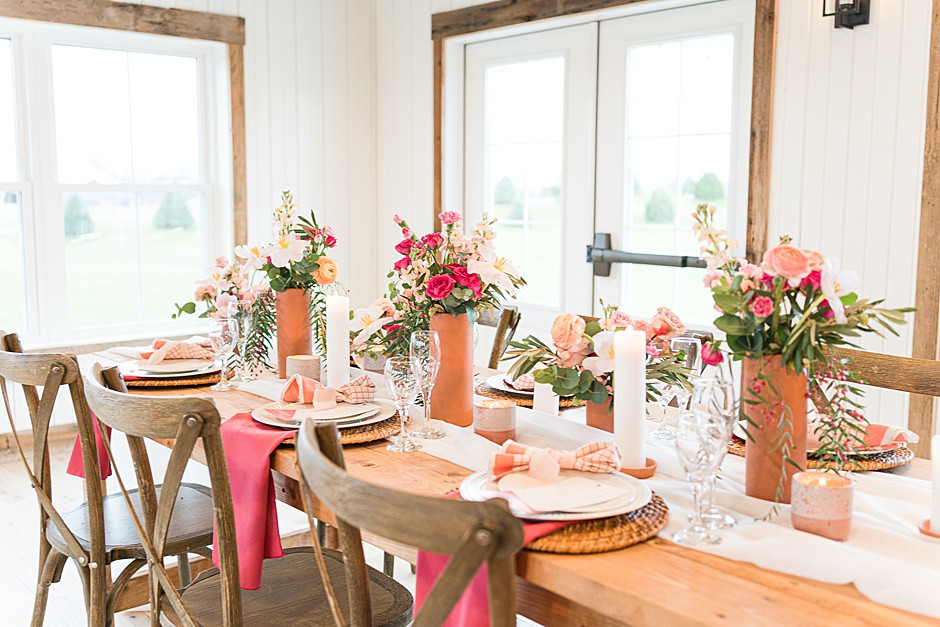 Wedding tablescape with bright pink flowers, yellow flowers, terracotta vases, white plates, peach napkins, white candles and glassware on a barnwood table with rustic barnwood chairs in a bright light wedding venue in Wisconsin