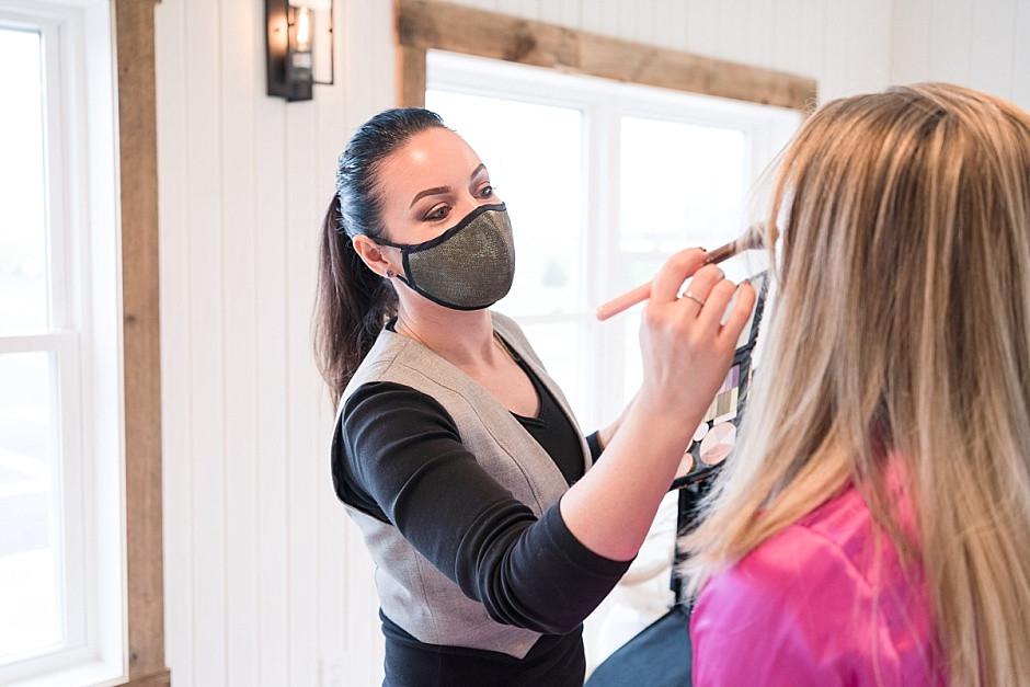 Makeup artist applying makeup to bride, bride getting ready photos
