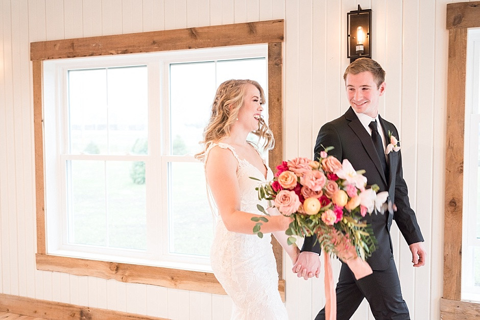 Bride and Groom walk happily with pink wedding bouquet smiling bride and groom