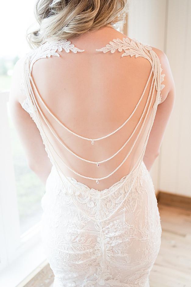 A wedding dress, a designer wedding dress with an open back, a wedding dress with lace, back of a wedding dress,in a bright light wedding venue in Wisconsin